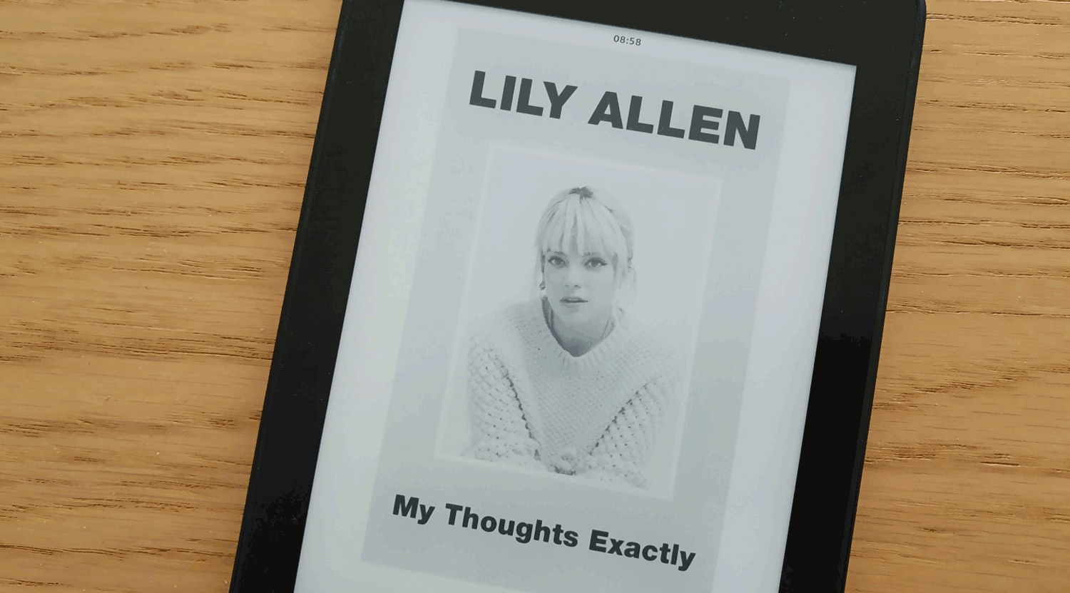 a kindle with the cover of the book My Thoughts Exactly by Lily Allen with a photo of Lily Allen over a wooden texture